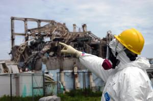 事故後の福島原発3号機と指差すIAEA調査員